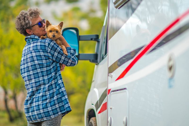 A woman carries her dog, a Yorkshire Terrier, in her arms as they stand outside an RV. She is wearing sunglasses and a plaid blue shirt. The dog is light brown and looking directly at the camera.