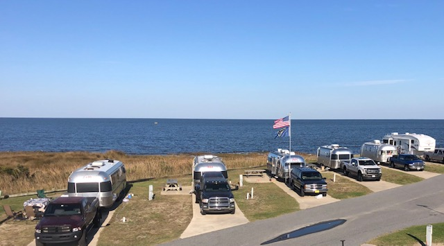 Multiple RVs are parked along the waterfront at Camp Hatteras RV Resort and Campground.