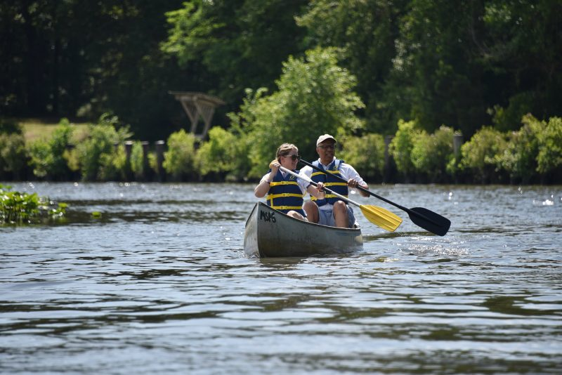 A man and woman wearing life vests canoe on a river at Pocomoke River State Park.