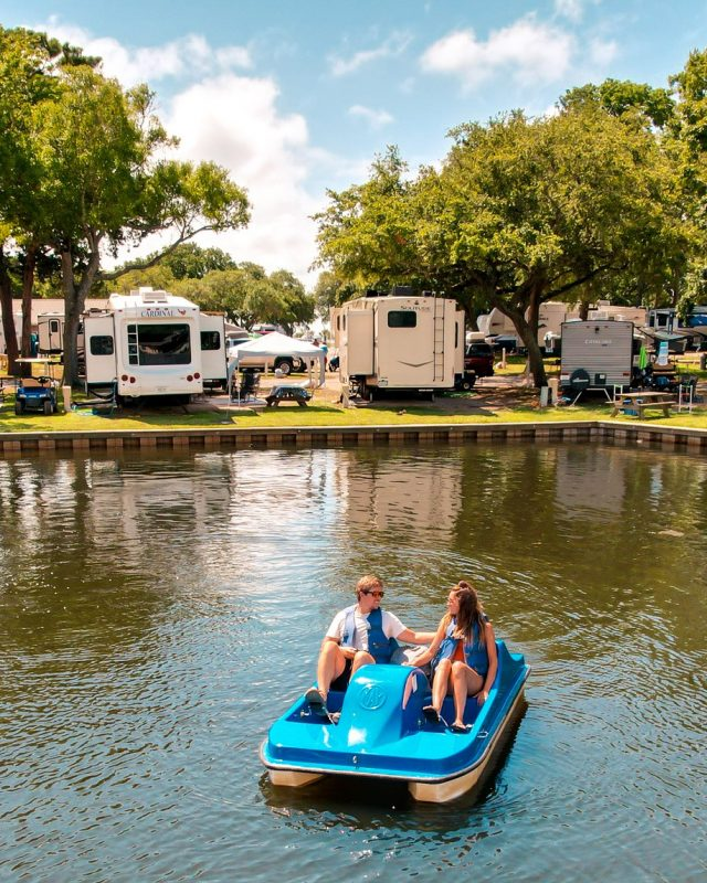 Two people use a paddleboat on the water while RVs are parked along the waterfront at Lakewood Camping Resort.