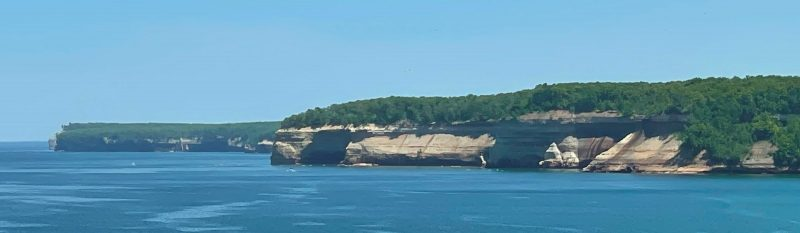 A landscape photo of Pictured Rocks National Shoreline shows the beautiful rock formations, lush green forest, and clear blue water.