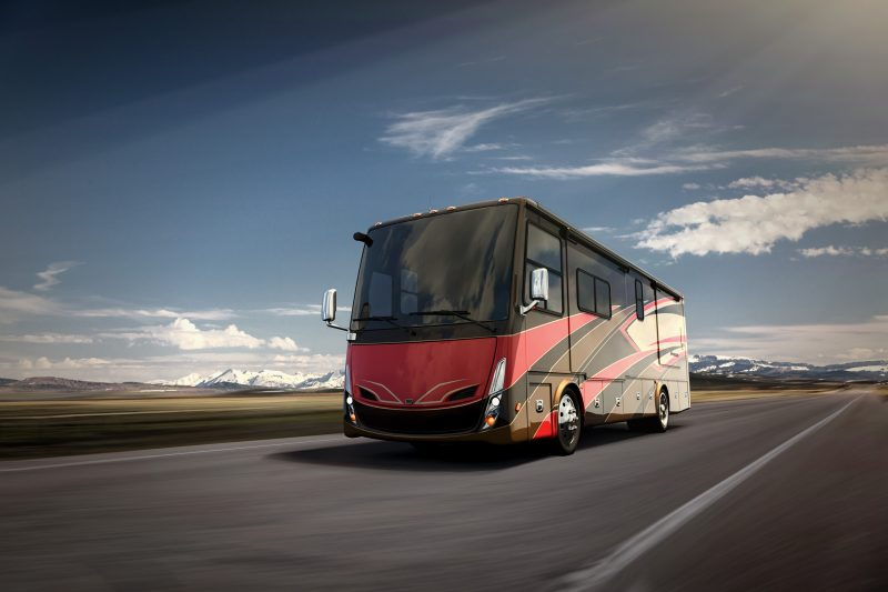 A modern Class A diesel RV with red, black, brown and tan colors travels down an open road.