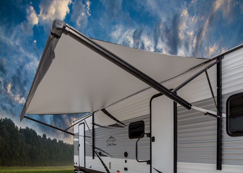 A Della Terra travel trailer is parked with it's awning extended. Clouds are scattered across the blue sky and a row of trees are behind the camper.