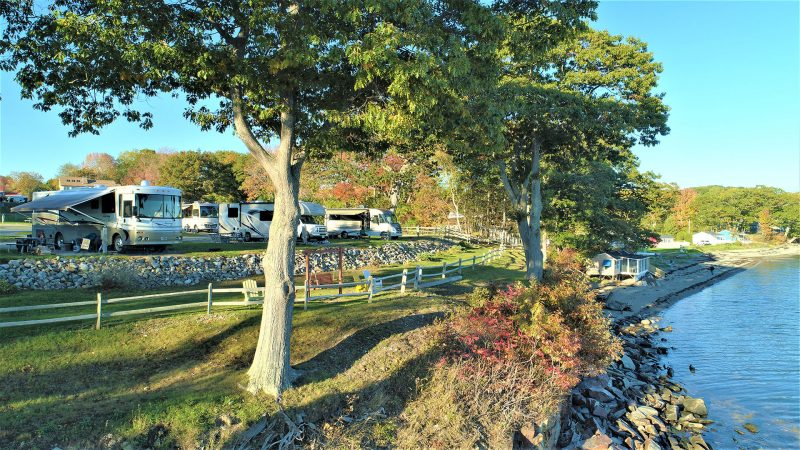 Multiple RVs are parked at a waterfront campground overlooking calm water.