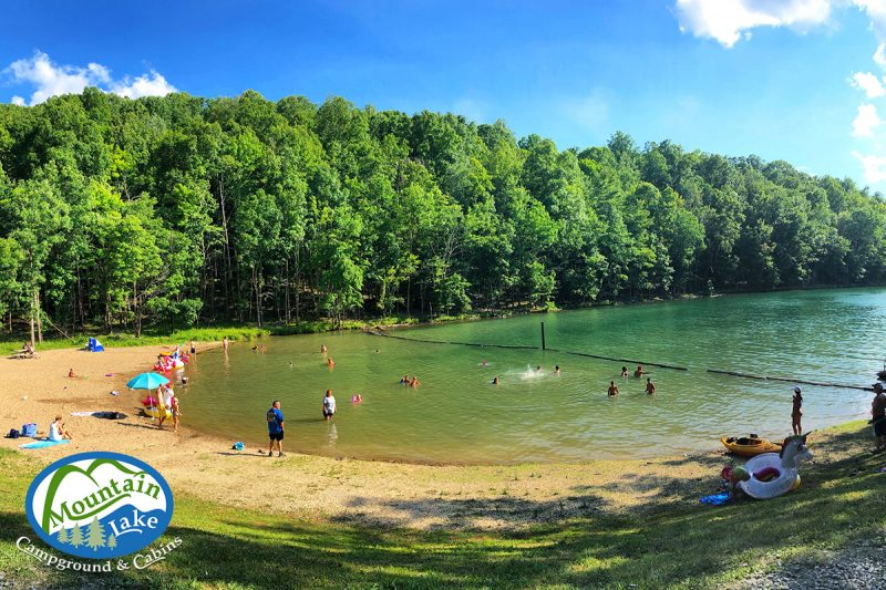Several people play on the beach and in the water at Mountain Lake Campground. The sandy beach is surrounded by mature forests.