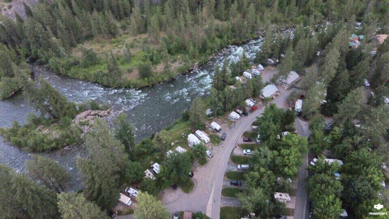 An overhead shot of the Icicle River RV Resort shows this waterfront RV park on the Icicle River and the surrounding green forest.