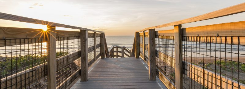 A wooden walkway leads to the beach at Beach Rose RV Park. The sun is rising over the water.