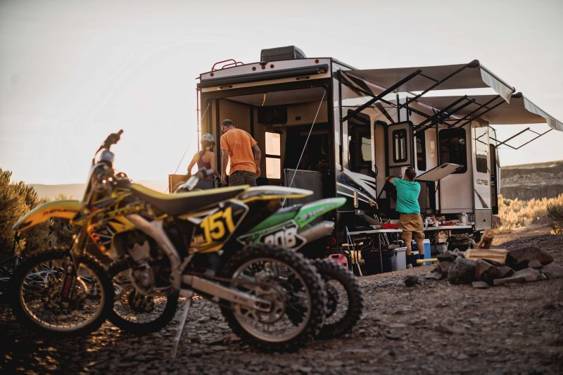 Two dirt bikes sit near a toy hauler RV