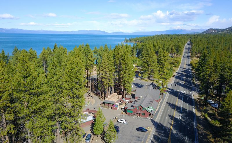 An overhead shot shows Zephyr Cove RV Resort on Lake Tahoe. This beautiful waterfront RV park is surrounded by tall trees and you can see the mountains in the distance.