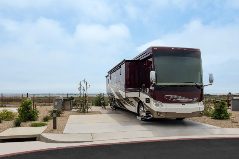 A Class A RV is parked at on a waterfront campsite at Sun Outdoors San Diego Bay. This waterfront RV park offers large campsites with concrete patios, picnic tables, and pristine landscaping.