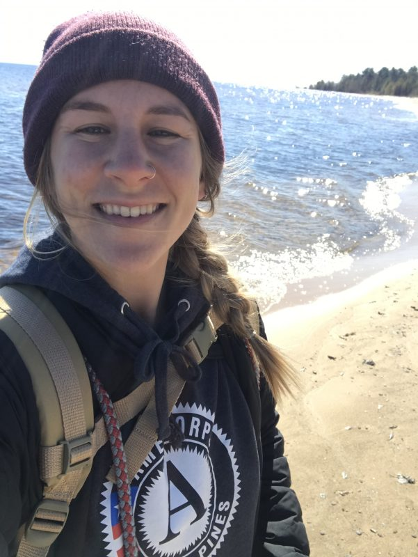 A selfie of Paige, the explorer behind Project Rustic, as she walks along a Michigan beach.