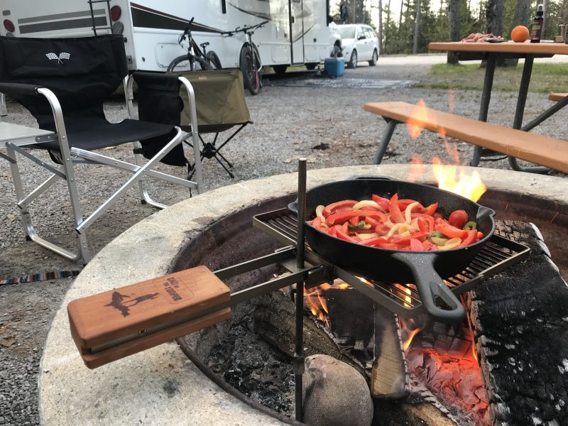 A cast iron skillet filled with chopped bell peppers and other vegetables cooks on a grill grate positioned over a campfire. In the background, an RV and vehicle are parked at a campsite. Two camp chairs are positioned near the fire.