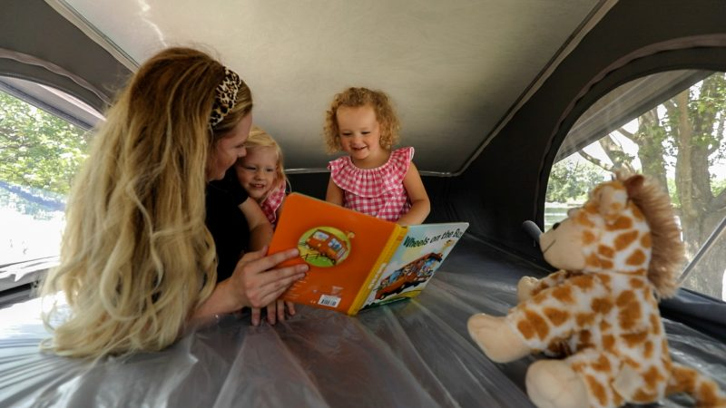 A mother reads to her two daughters while they lay on a bunk bed inside an RV.