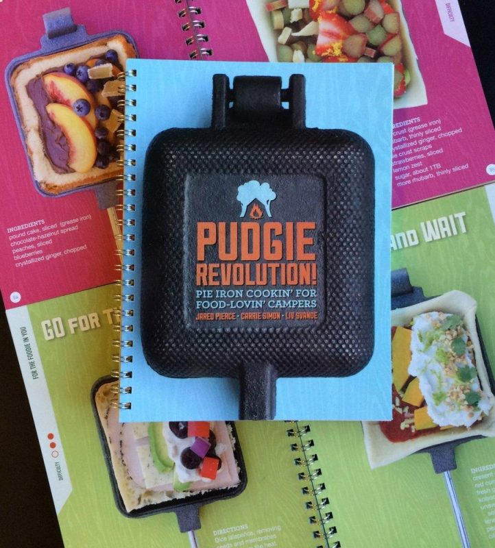 The colorful cover of the Pudgie Revolution Pie Iron cook book includes photos of various recipes and a cast iron pie iron that can make them all.