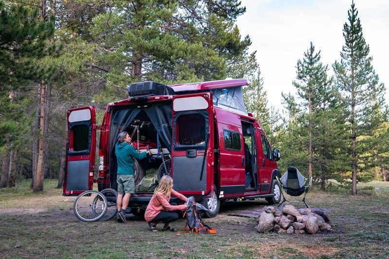 Couple prepares campsite by unloading gear from Winnebago Solis Pocket