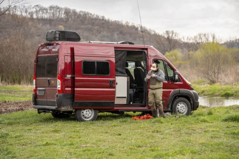 A man wearing waders and a hat stands outside a red Winnebago Solis Pocket preparing to go fly fishing. The RV is parked in a grassy, wooded area near a body of water.
