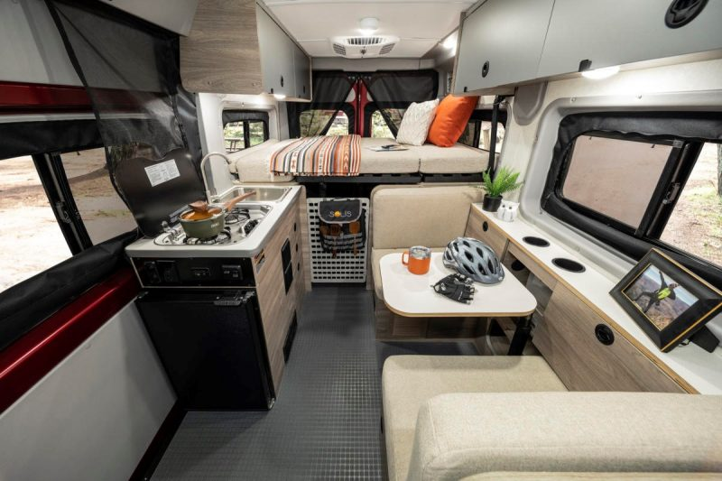 The interior of the Winnebago Solis Pocket has a dining/lounge area across from the galley and raised platform bed at the rear of the coach.
