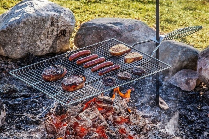 A grill rack filled with food - including burgers and hotdogs - cooks over a campfire.