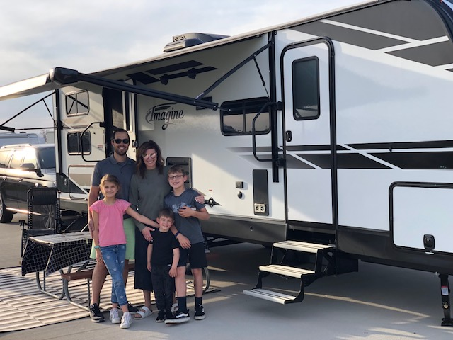 A family consisting of a man, woman, and three children stands in front of a travel trailer RV parked near a picnic table.