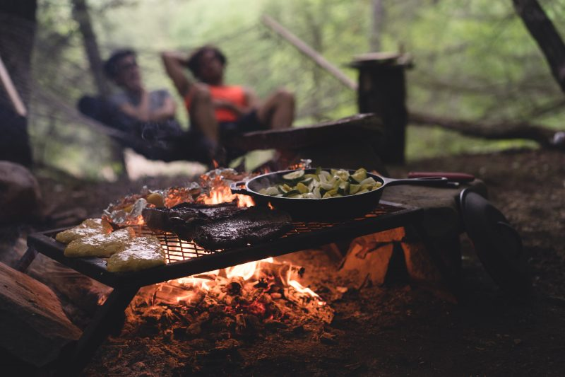 Two people in a hammock watch a fire with food cooking at a campsite.