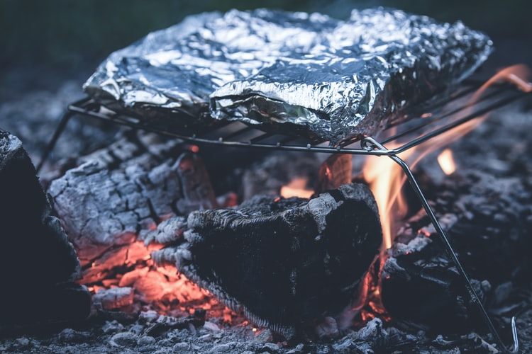 A pair of foil-packet meals cooks on a grill grate over a campfire. Foil packet meals are simple campfire recipes that are as easy as throwing all the ingredients into a piece of foil, folding the foil into a rectangular shape and cooking over a campfire.
